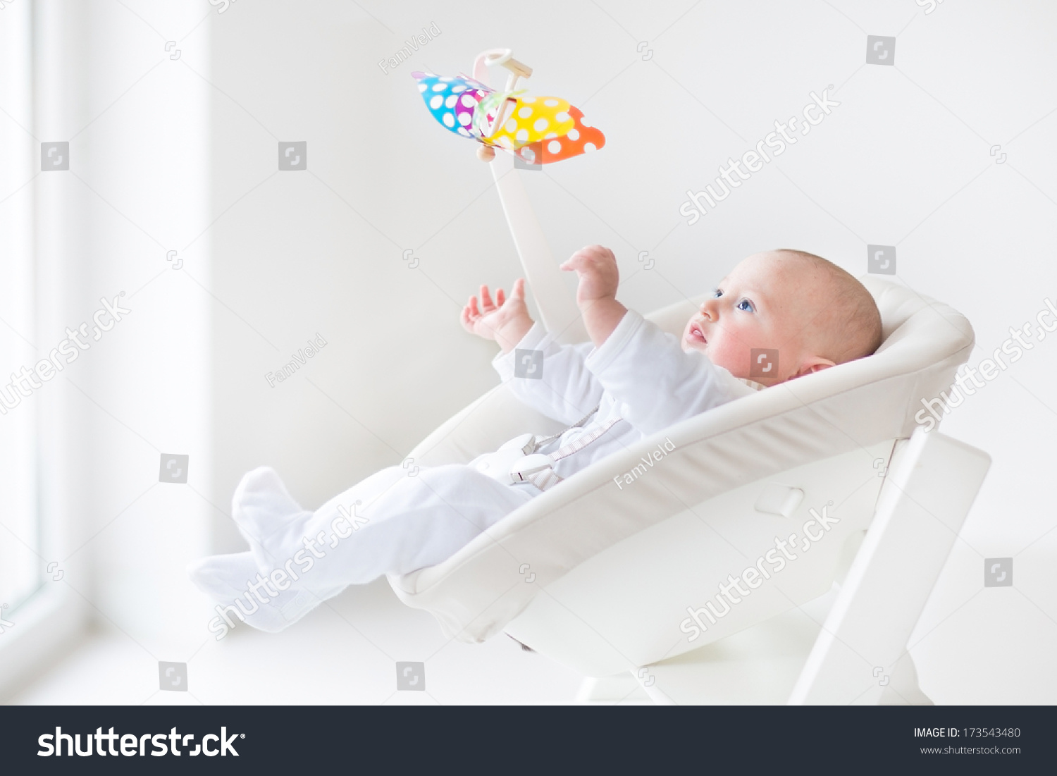 baby sitting chair india best for reading nook cute newborn boy watching a colorful mobile toy