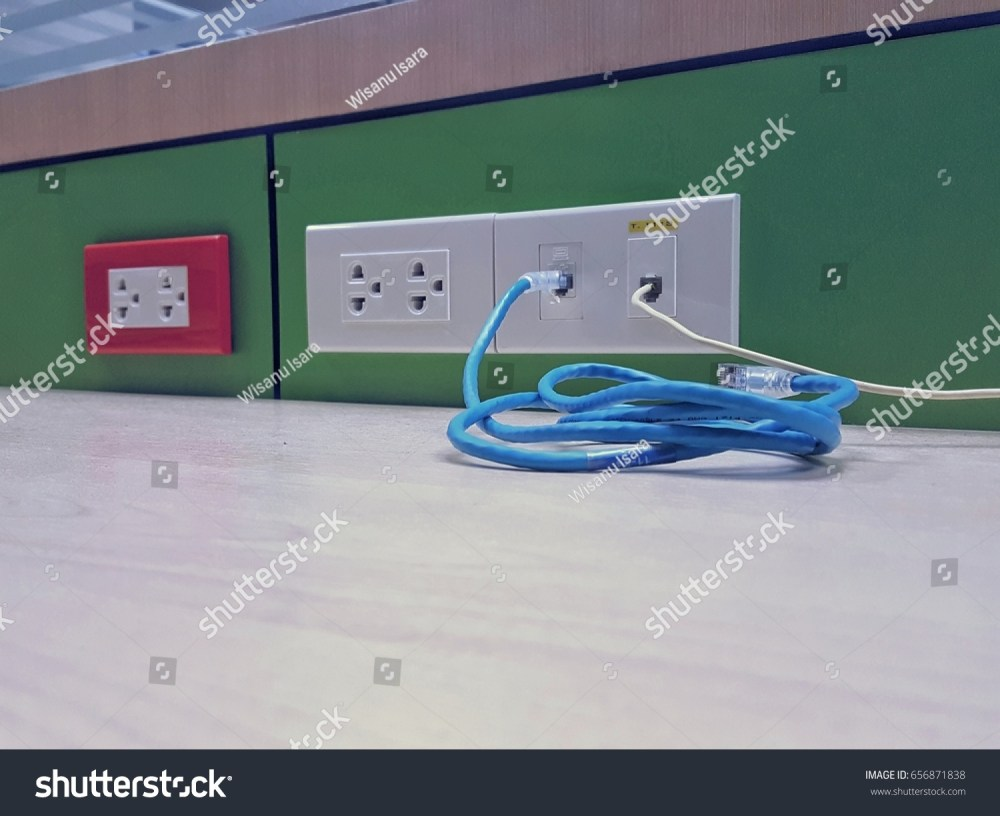 medium resolution of electric plug in red and white casing cover with network and telephone plug on green wooden wall