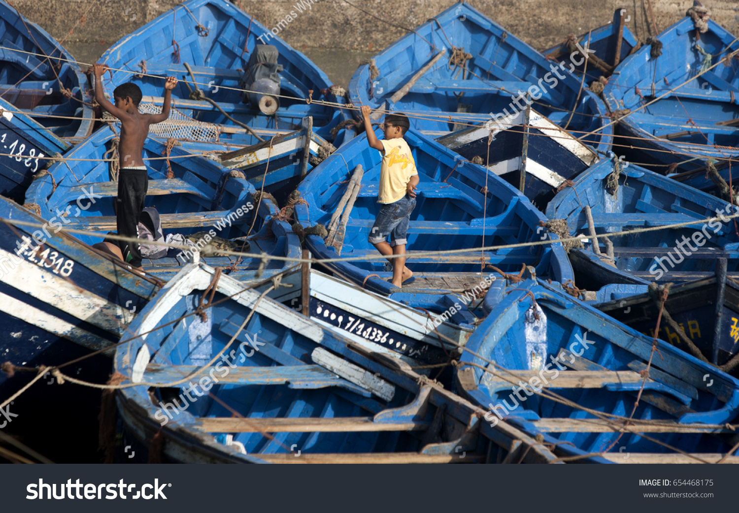 hight resolution of essaouira morocco august 02 2013 boys stand amongst docked fishing boats in