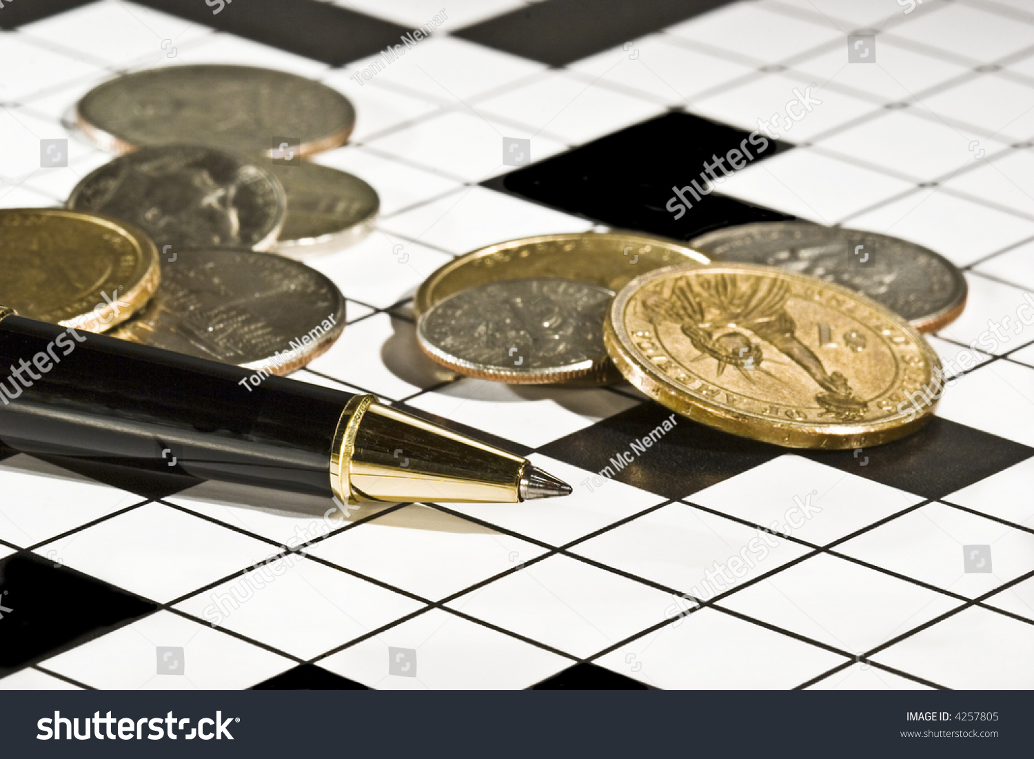 Executive S Ballpoint Pen And Coins On A Blank Crossword Puzzle Conceptual Image For Money