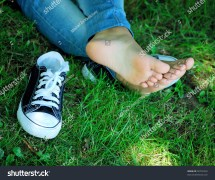Feet Of Girl Teenager And Gym Shoes Green Grass