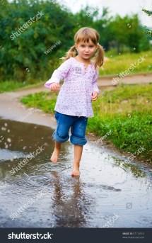 Girl Junps Barefoot In Puddle Splashing Water