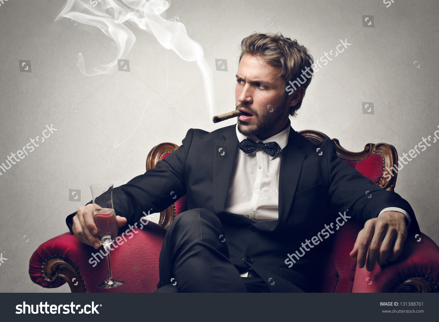 Handsome Boss Sitting On The Armchair Smokes Cigar Stock