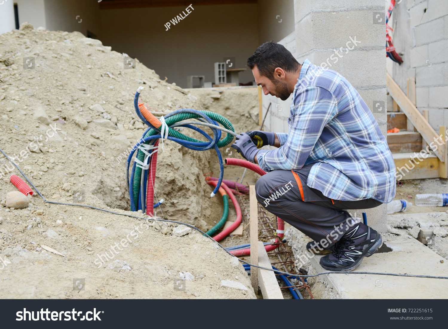 hight resolution of handsome young man electrician wiring cable outdoor in a house building construction site
