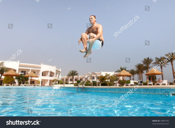 Man Jumping In Swimming Pool. Angle View