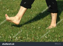 Man Walking Barefoot in Grass