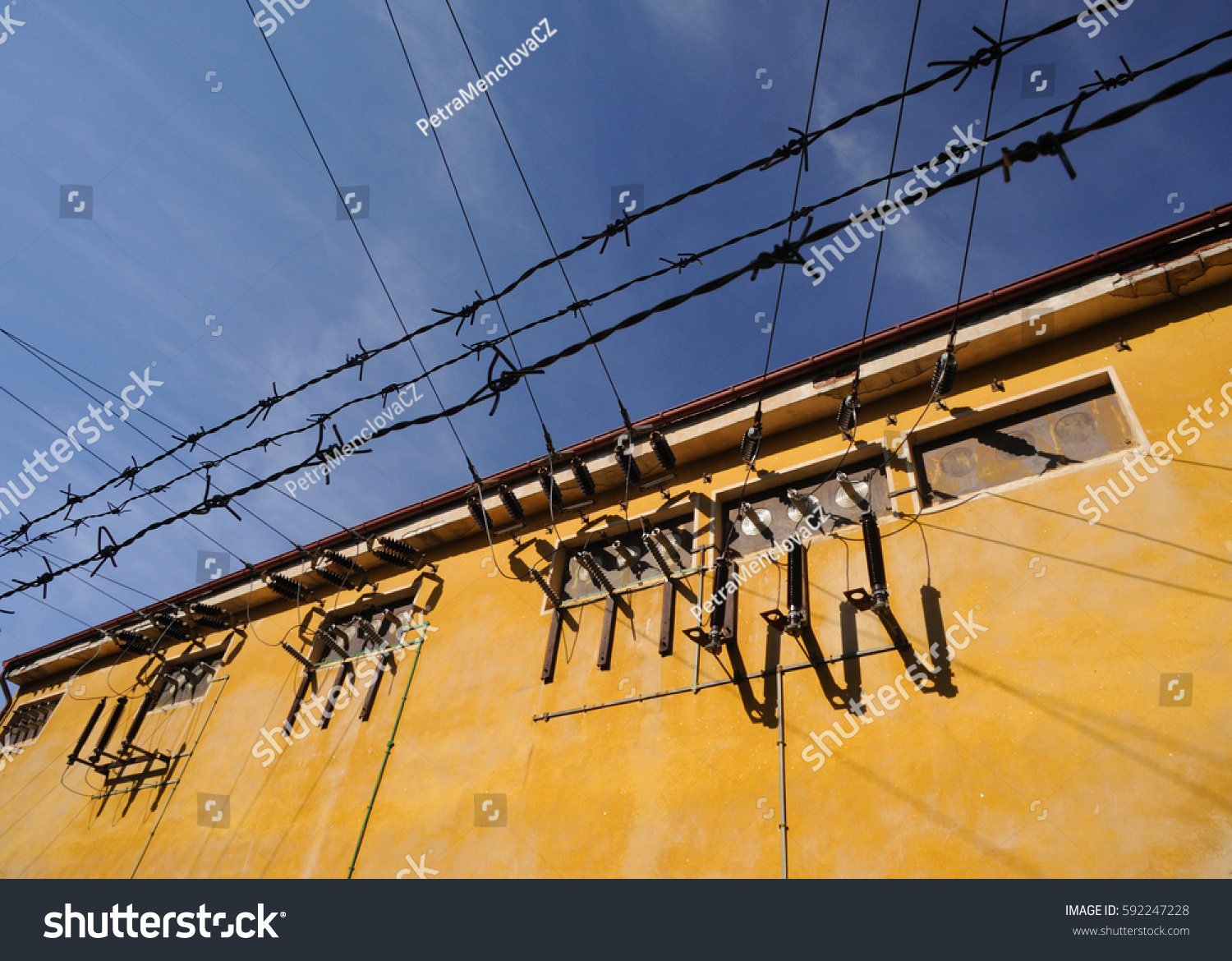 hight resolution of old transformer building with transformer points in sunny day clean blue sky background barbed