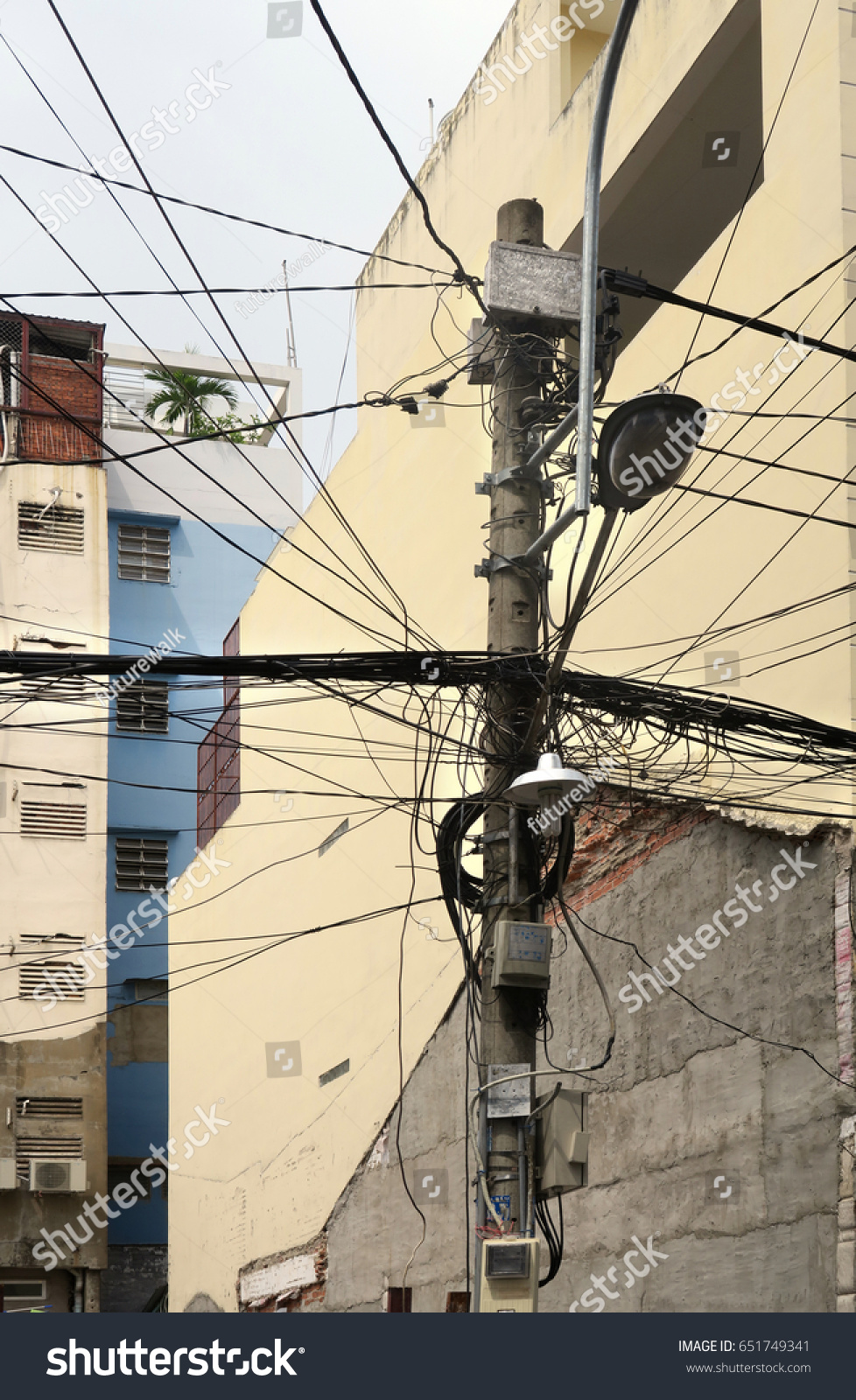 hight resolution of residential power supply tangled wires on a telephone pole for supplying neighboring apartment buildings with electricity in downtown saigon vietnam