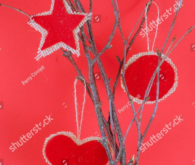Rough Textured Homemade Red Felt And Burlap Ornaments Hanging On Bare Twigs Are A Rustic