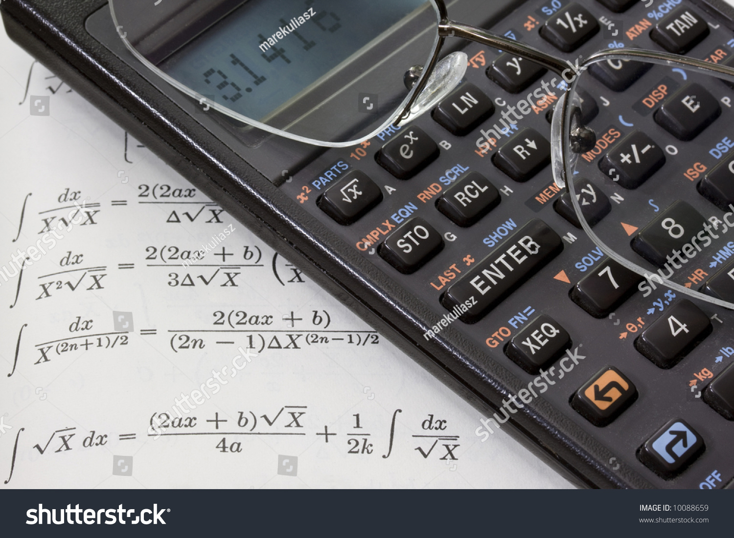 Scientific Calculator With Pi Number On A Display And Reading Glasses Against Math Text Book