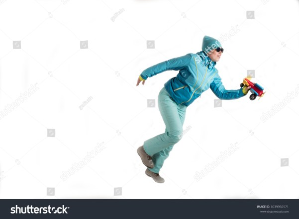 Slender young girl in blue ski suit with toy airplane in her hands posing for sculptor. The concept of sport lifestyle. Busy schedule of young business woman. Collection of sportswear. Pilot style by Shutterstock contributor galitsin