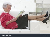 Smiling Elderly Woman Reading Sofa Stock