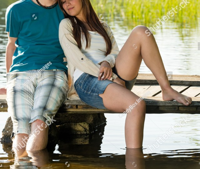 Teen Couple Sitting On Pier With Legs In The Water