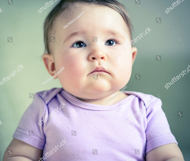 Thoughtful And Serious Nice Baby Indoor Ten Month Old Cute Child Closeup Portrait Of Chubby Baby Girl In Purple Clothes Face Of Adorable Toddler On The