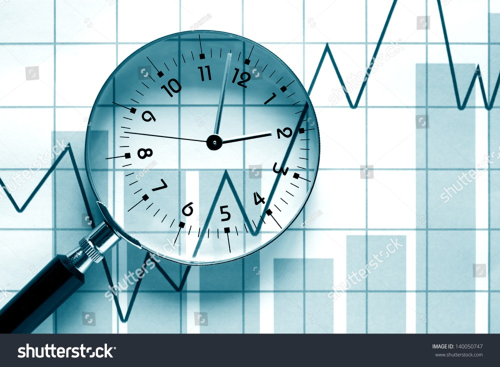 medium resolution of clock face inside magnifying glass on background with business chart
