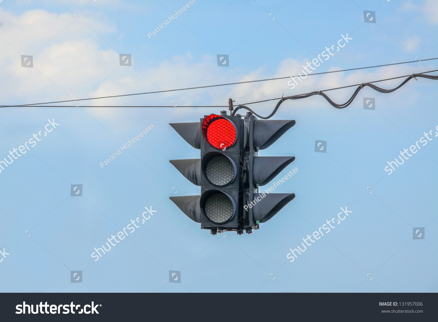 hight resolution of traffic light on red hanging on wires in the air