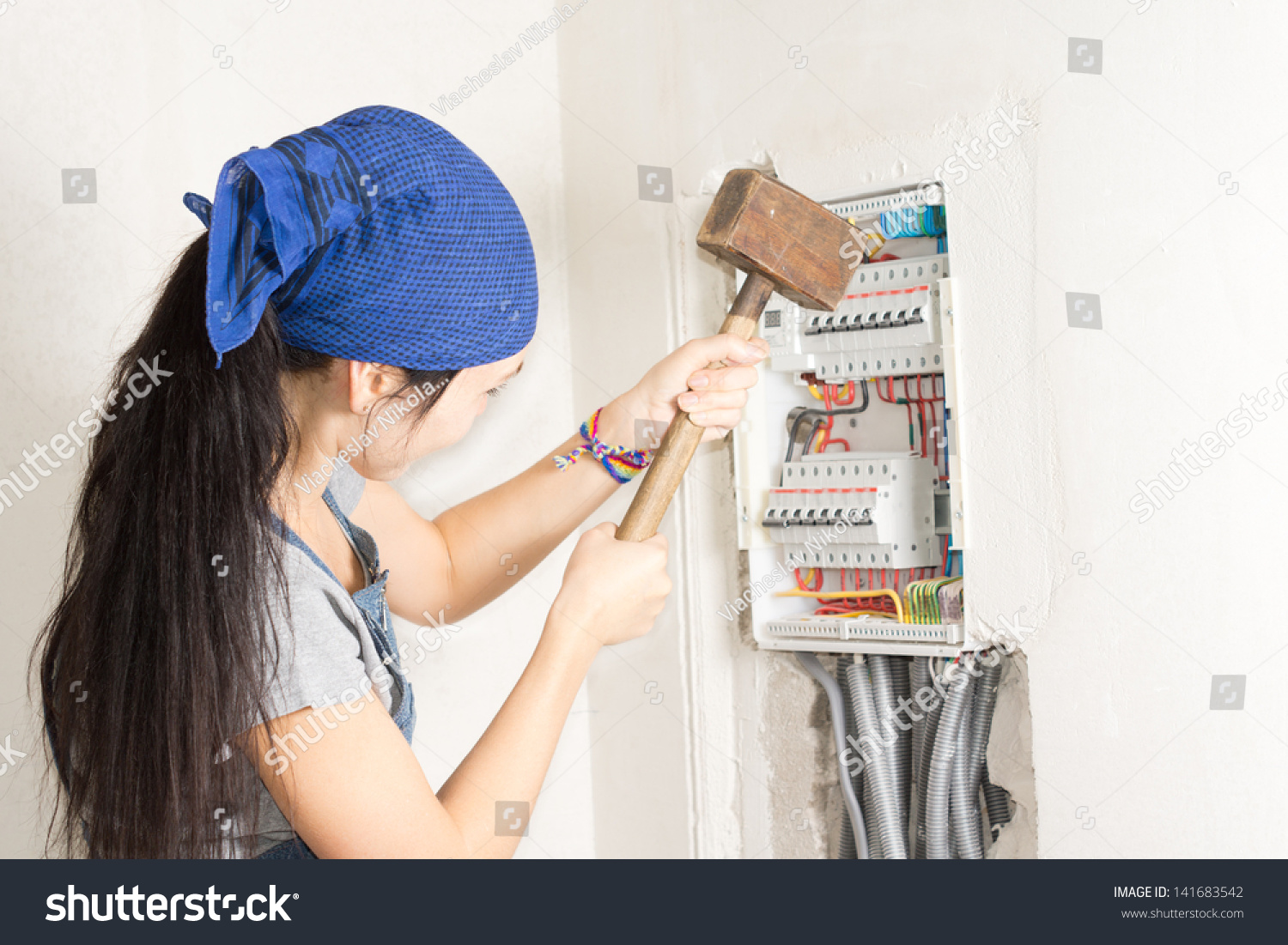 hight resolution of woman taking aim at an electrical fuse box with a large wooden mallet in an effort