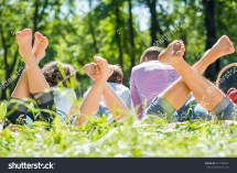 Young Happy Family Lying In Park Barefoot Stock