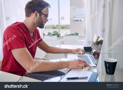 small resolution of young professional busy working in his home office on his
