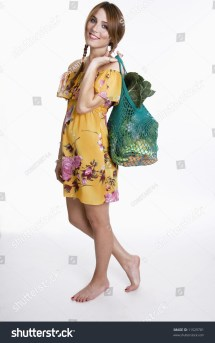 Young Woman Standing Barefoot Carrying Green Grocery Bag