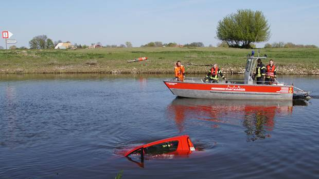 Rescue workers recover a car from the harbor basin in Bleckede