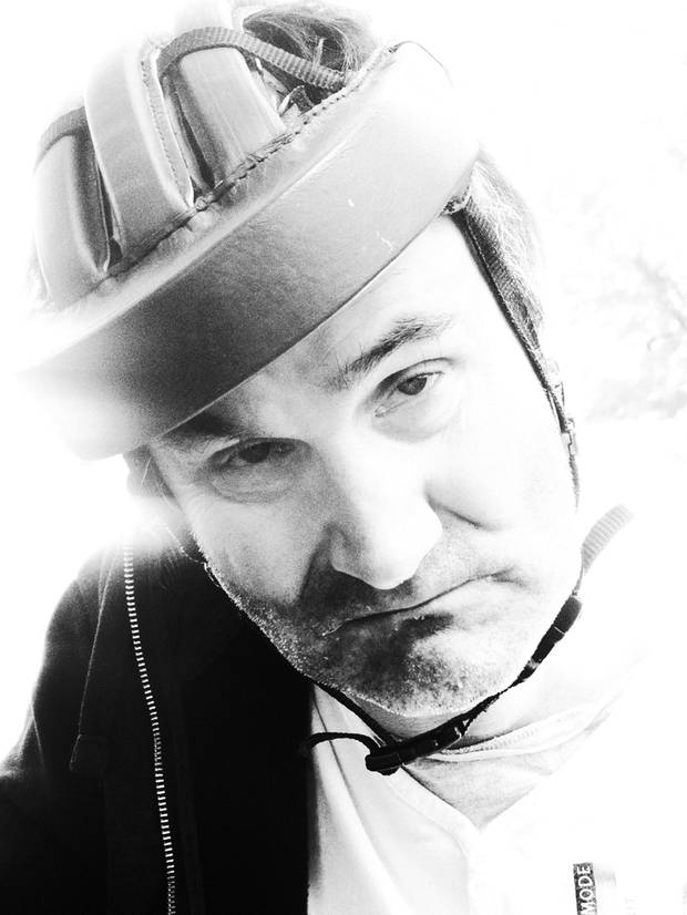 A man with a protective helmet looks into the camera