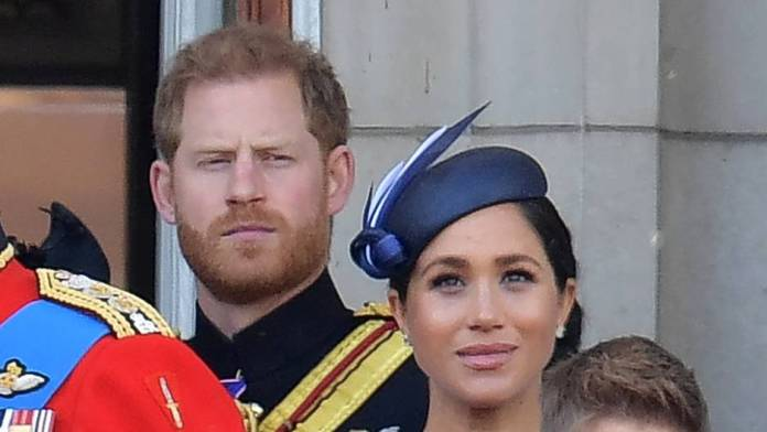 Prince Harry stands behind his wife, Duchess Meghan, and looks stern