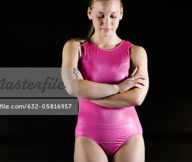 Female Gymnast Standing With Arms Folded Across Chest Looking Down In Disappointment Stock Photo