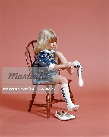 little girl chairs unusual chair uk 1960s 1970s blond sitting on dressing herself pulling knee socks stock