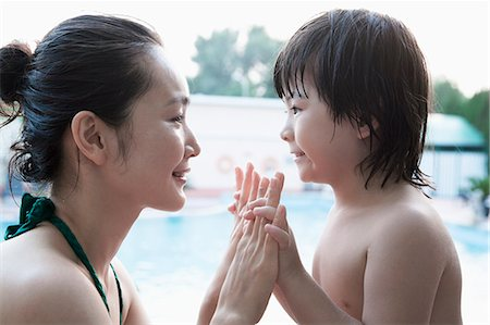 Smiling Mother And Son Face To Face And Holding Hands By The Pool Stock Photo