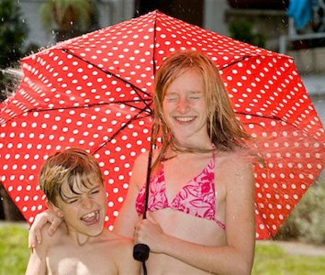 Two Children Standing Under An Umbrella And Getting Hit By Spraying Water Stock Photo Premium