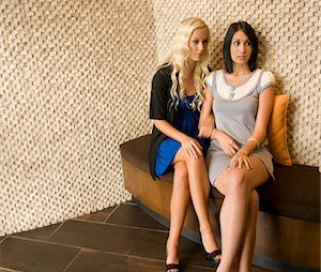 Seducing Ladies Crossing Legs Two Young Women Sitting On Bench In Modern Interior Stock Photo