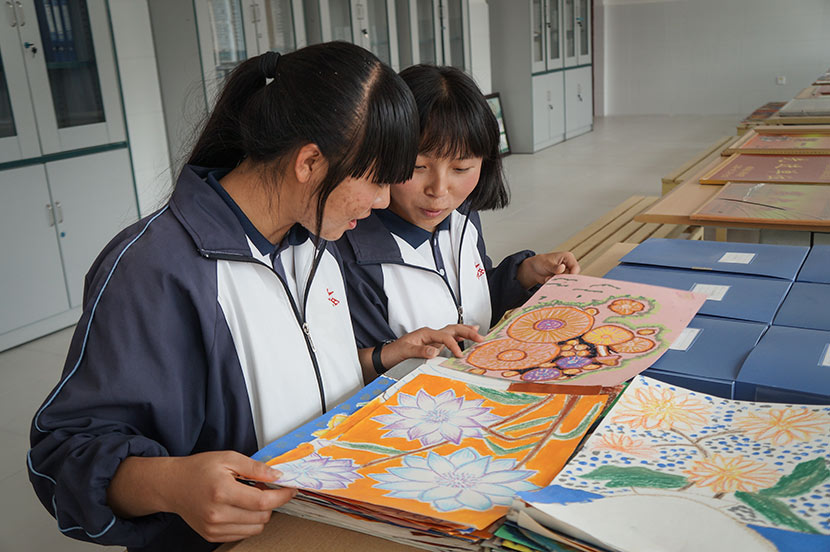 Zhi Zhengjiao (left) and Chang Ranran look at works of art created by their classmates at Nanjian No. 2 Middle School in Nanjian Yi Autonomous County, Yunnan province, March 22, 2018. Fan Yiying/Sixth Tone
