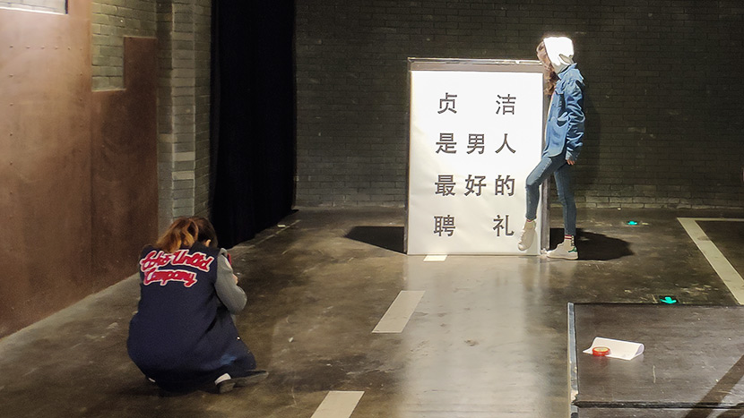 "A visitor poses next to a white posterboard that reads: ""Virginity is a man's best betrothal gift,"" at Wu Kangyang's exhibition in Chengdu, Sichuan province, Oct. 24, 2018. Fan Yiying/Sixth Tone"