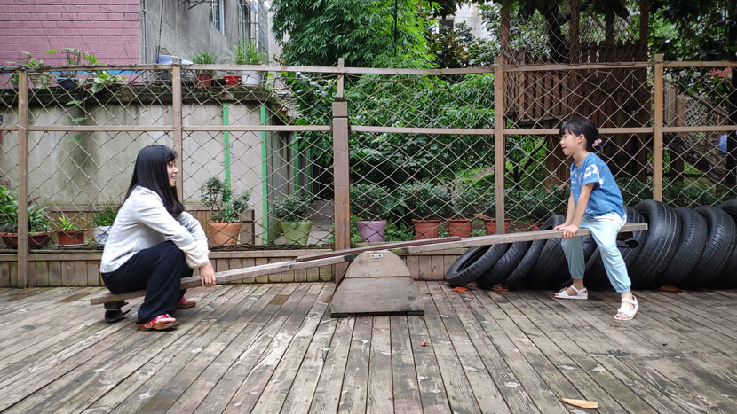 Deng Sha plays on the seesaw with her daughter at Xiyanghong, Guiyang, Guizhou province, June 17, 2019. Fan Yiying/Sixth Tone