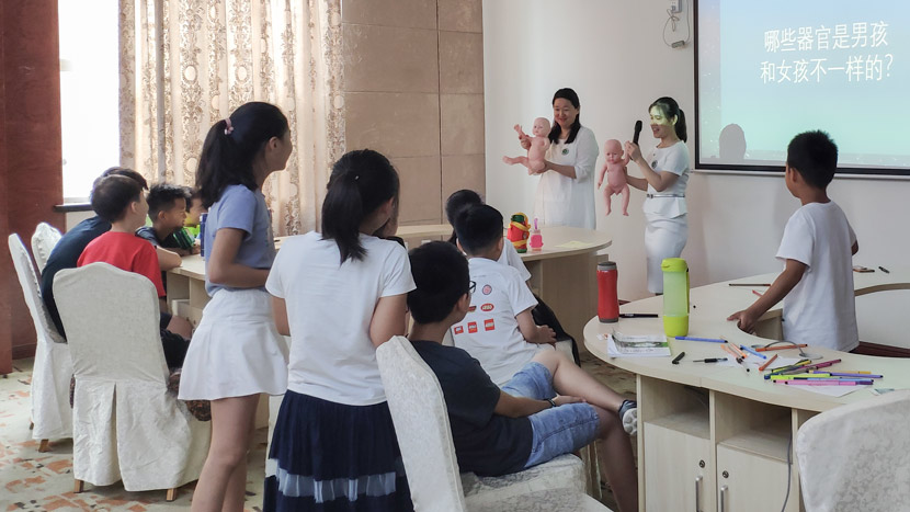 Sex education lecturers Wang Yi (left) and Jiang Lingling (right) show children male and female organs on dolls during a sex education summer camp in Qingdao, Shandong province, Aug. 2, 2019. Fan Yiying/Sixth Tone