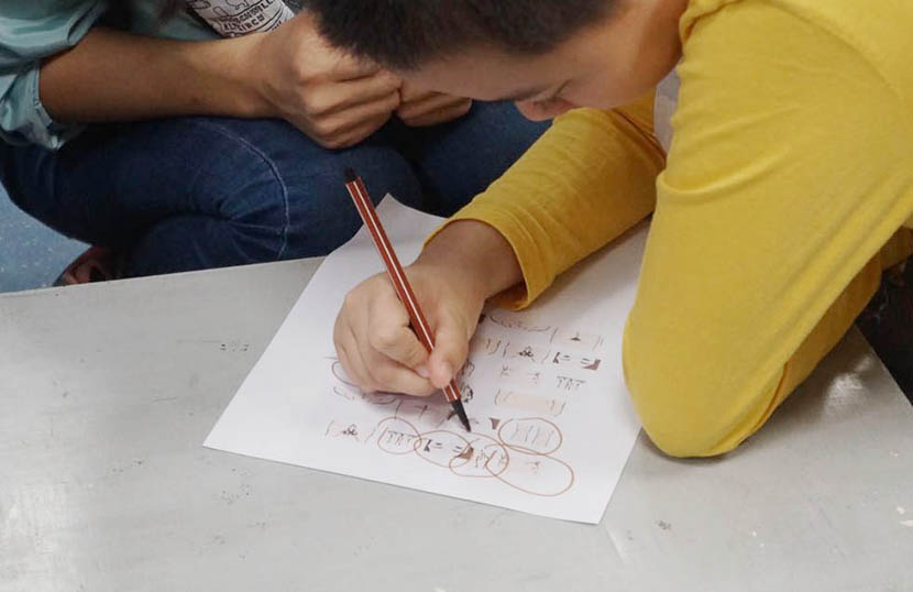 A boy with autism circles private parts on a worksheet during a sex education class at No. 2 Children's Palace, Guangzhou, Guangdong province, Nov. 5, 2017. Fan Yiying/Sixth Tone