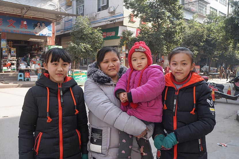 Long Xiaomei and her daughters pose for a photo in Guxian Town, Sichuan province, Jan. 10, 2018. Fan Yiying/Sixth Tone