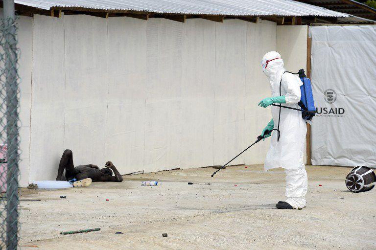 Homem nu, infectado por Ebola, é observado por agente de saúde na Libéria / Pascal Guyot/AFP