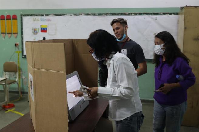 Votantes con mascarillas por la pandemia de COVID-19, en un centro electoral de Caracas, durante las elecciones legislativas de Venezuela.
