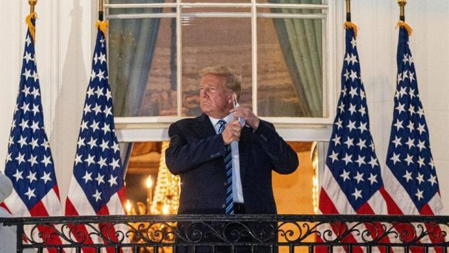 El presidente de EE UU, Donald Trump, se quita una mascarilla al saludar desde un balcón de la Casa Blanca, tras regresar a su residencia después de ser hospitalizado por COVID-19.