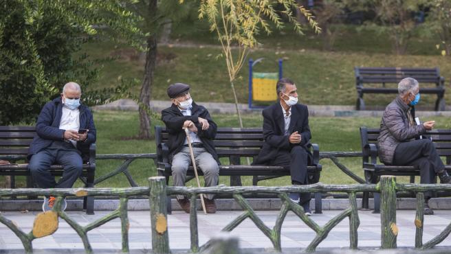 Hombres con mascarilla en un parque de Teherán.