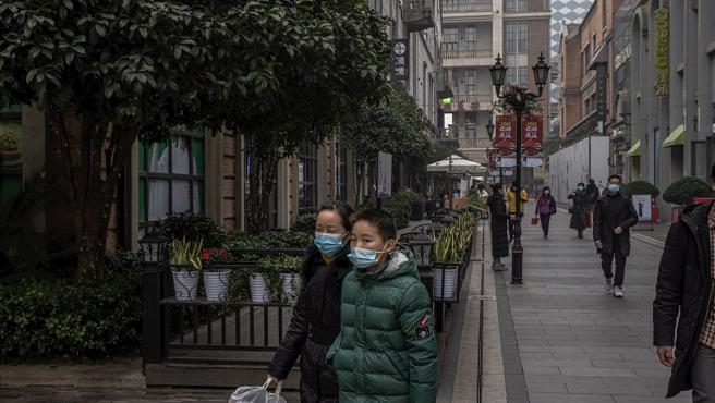 Varios viandantes pasean con mascarillas en una zona comercial de Wuhan, un año después de que se detectase allí el coronavirus.