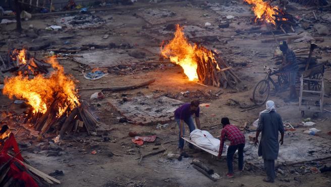 Varias personas transportan el cuerpo sin vida de una víctima de coronavirus a un campo de cremación improvisado en Nueva Delhi.