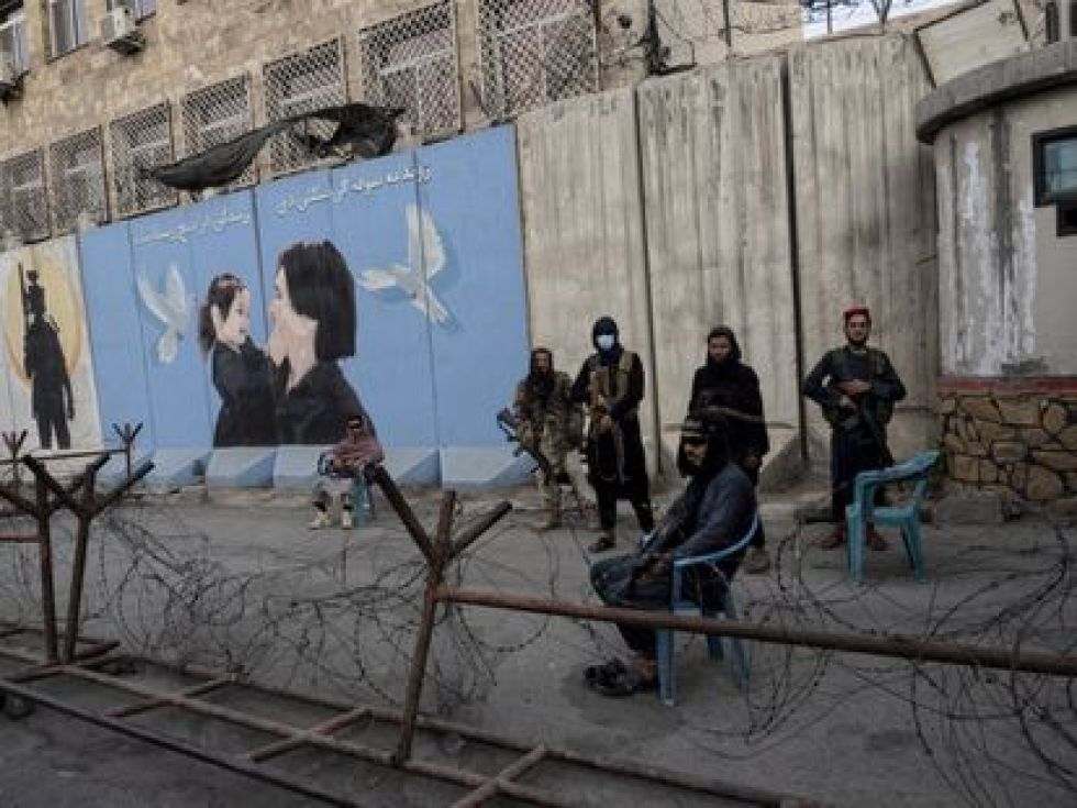 A group of Taliban stand guard in Kabul before a poster depicting a woman and a girl.