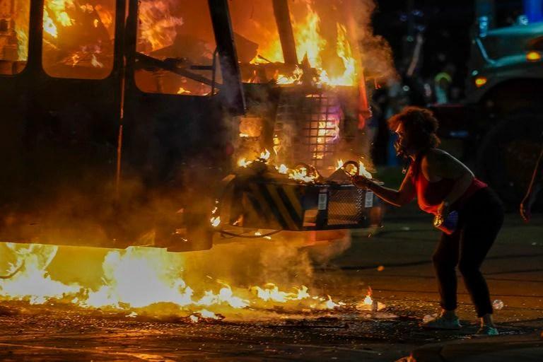 Una manifestante enciende un cigarillo en un camión de basura, presa de las llamas durante las protestas del lunes por la noche en Kenosha (Wisconsin).