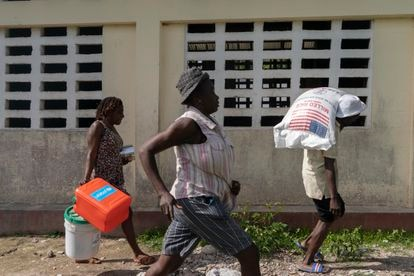 A group of people runs to receive food.