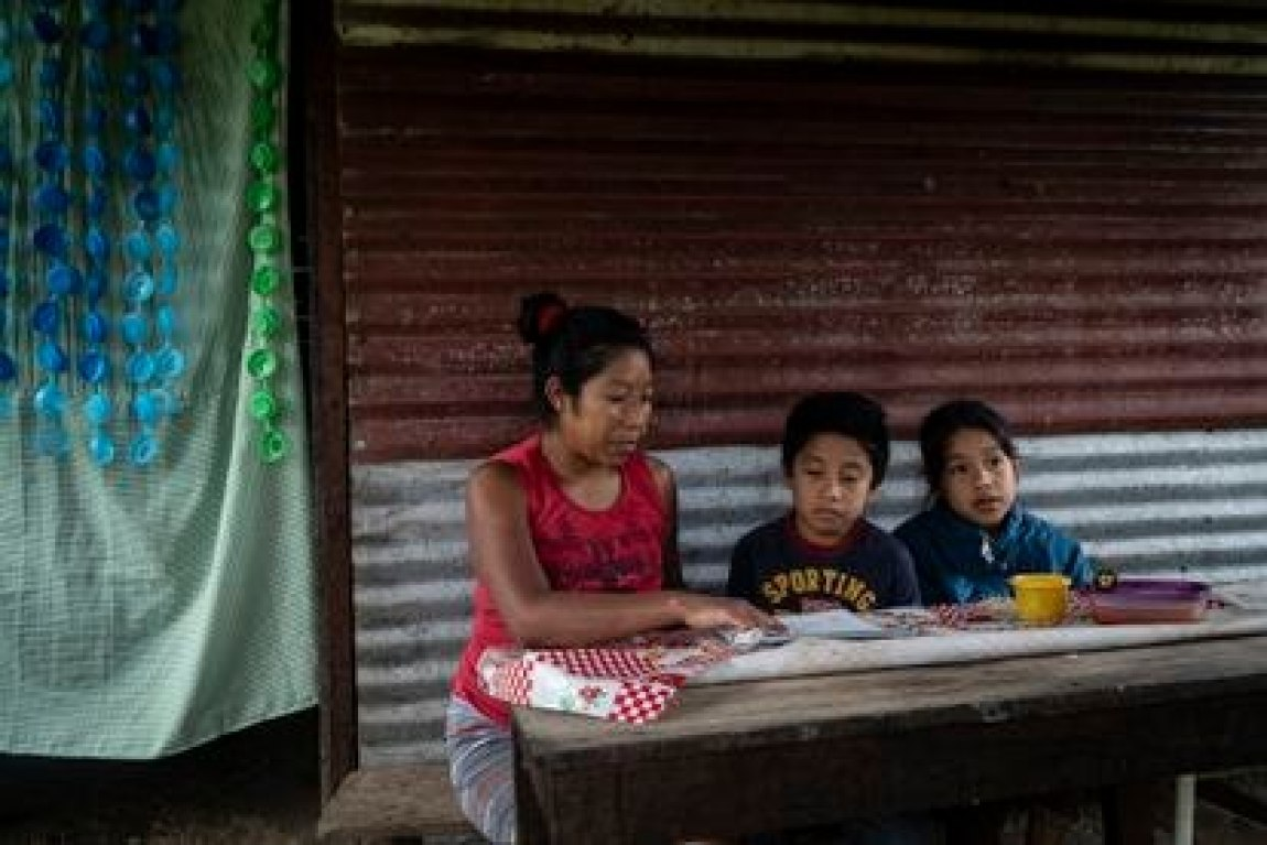 Claudia Gomez helps her children to study, who stopped attending face-to-face classes due to the pandemic, in the municipality of Ocosingo, Chiapas.