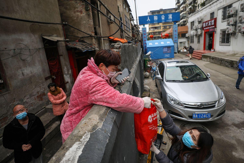 Una persona recibe una bolsa de comida en Wuhan, el 3 de marzo.