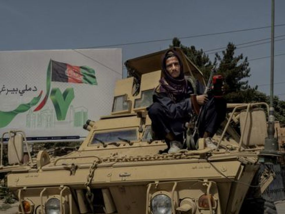 A Taliban militiaman sits on a captured tank watching Afghan troops in one of the bases abandoned by the Army.
